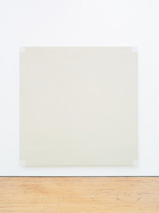 A square, light-gray painting includes four white squares in each corner.