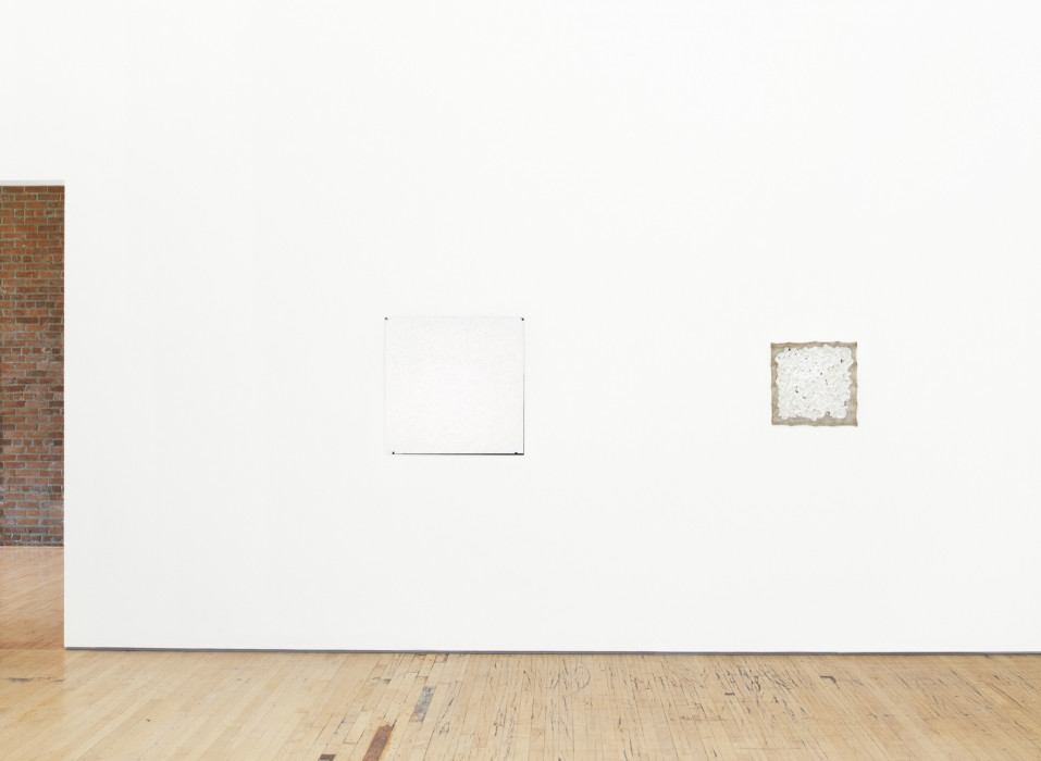 Two small square white paintings hang on a white wall above a wood floor.