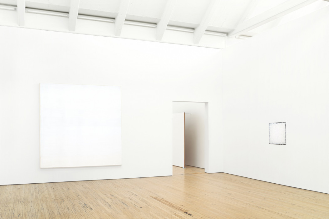 Two square white paintings hang on white walls above a wood floor. The one on the left wall and the right one is small. A large, rectangular white painting affixed to a wall by long metal rods and resting on the wood floor is partially visible through a doorway between the paintings.