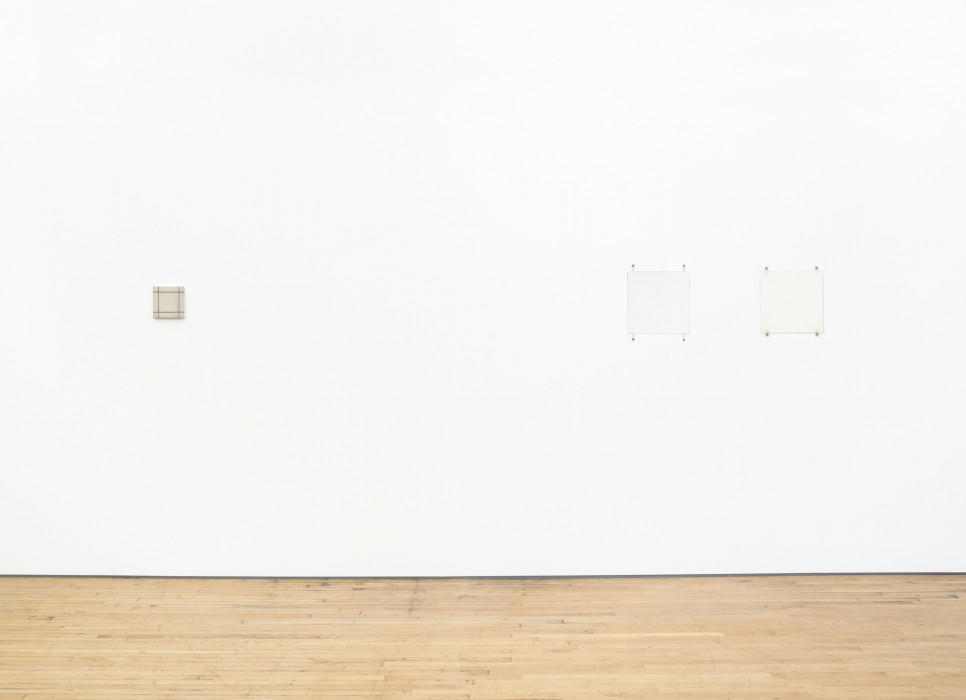 Three square paintings hang on a white wall above a wood floor. The far left painting is small and tan with a grid of black lines. The two white paintings on the right hang close together and are affixed with fasteners and bolts.