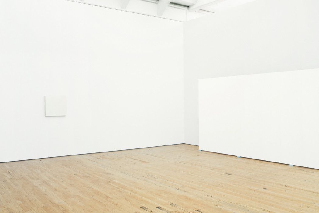 A small, square white painting hangs on a wall above a wood floor. A partially visible, large, rectangular white painting rests on blue pads on the floor near the wall to the right.