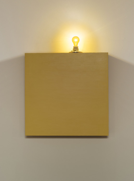 A yellow box topped with a yellow lightbulb hangs on a white wall.