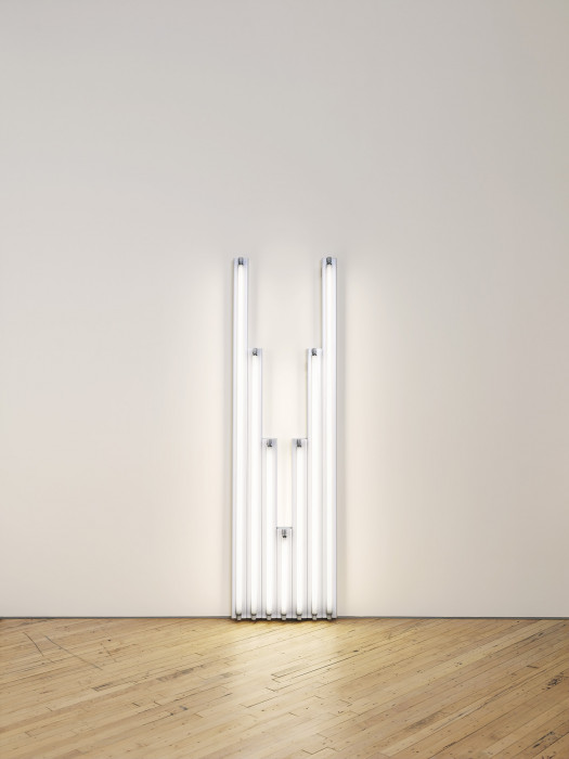 Seven fluorescent-white, tubular lights positioned against a white wall, four of which are arranged in descending order from tallest to shortest, shortest light at center is followed by three more lights arranged in ascending order from shortest to tallest.