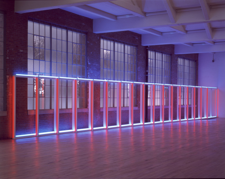 Flourescent tubes form a horizontal ladder with 18 rungs against a wall in front of large windows. The room is dark except for the neon light; the horizontal tubes are white, and the vertical tubes are red.