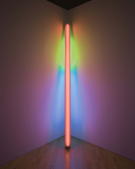 A long, orange, fluorescent lightbulb leans against an illuminated corner of a room that appears green, blue, and pink.