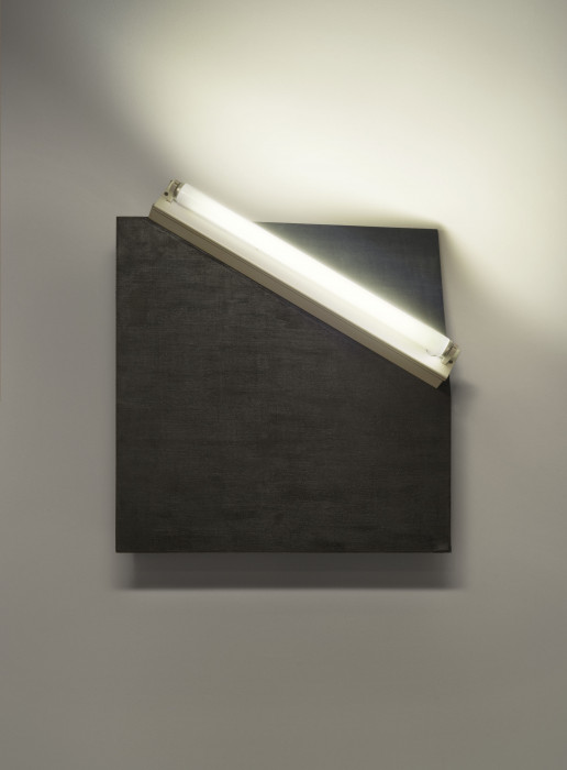 A white fluorescent tube lays diagonally across a black square mounted on a wall. The upper right corner of the square is bent backwards.