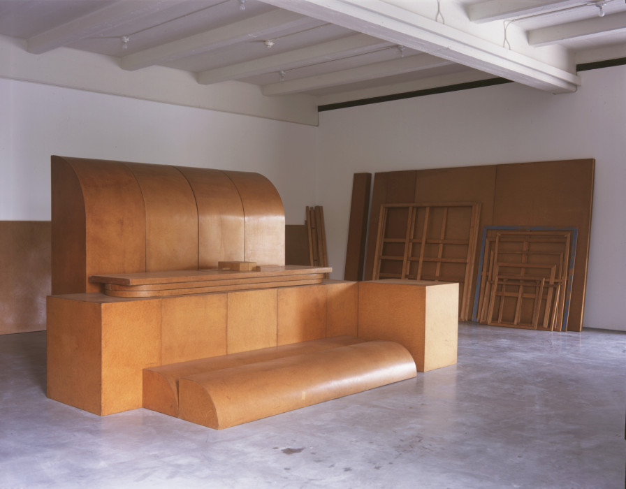 Large, smooth, curved wooden shapes and cubes abutt and pile atop each other in the center of a room, with wooden panels and empty frames leaning on the walls, all stained a reddish brown.