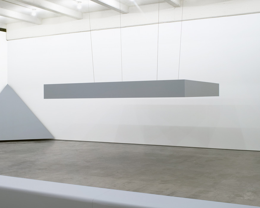 A horizontally oriented, tabletop-like, gray sculpture is suspended from the ceiling.