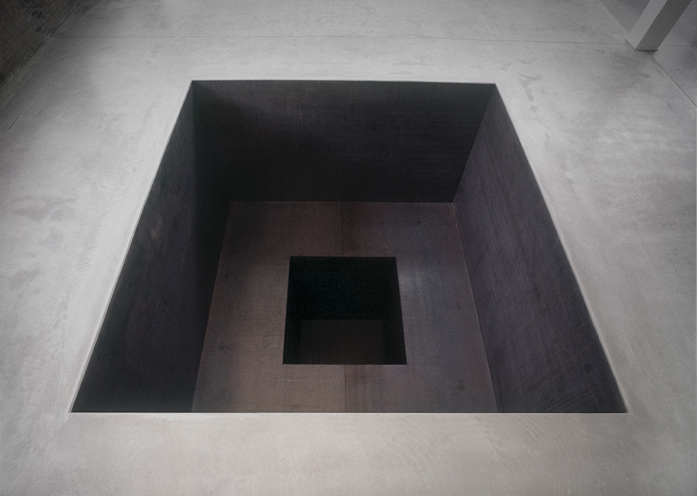 Negative space is carved into a cement floor in the shape of a square. A second smaller square is carved into the first and further recedes into the floor.