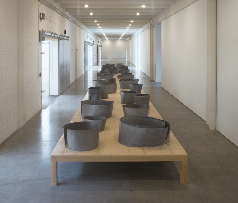 A low wooden table, on which many small, circular, metal shapes are placed in two rows, sits in a hallway.