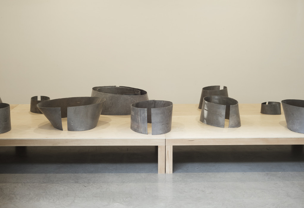 A partial view of two low wooden tables on which circular, metallic shapes are placed in two rows.
