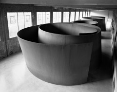 Large square windows are evenly spaced along one wall of an industrial room where a row of four large, curved sculptures consume the visible space in this black-and-white image.