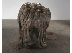 An irregularly shaped, bronze sculpture with circular structures coming out of its base is placed on a cement floor.