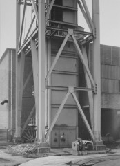 Black-and-white photograph of a large vertical tower encased in an open-air metal support structure, outside a rectilinear brick building.