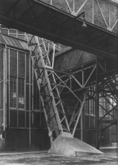 Black-and-white photograph of brick factory building featuring an open-air diagonal metal support structure and an aboveground upper-story brick passageway.