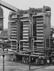 Black-and-white photograph of three vertical cooling towers with a vertical stack of half-cylindrical forms attached to the front and intersecting tubes connecting each tower.