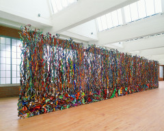 Freestanding tall curtain-like sculpture composed of multicolored thin, twisting vertical metal strips.
