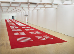 A series of many white hexagonal poles are horizontally placed on a red carpet that spans the length of a large white room with a wooden floor.