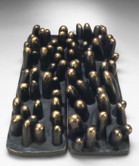 A rectangular, black base is topped with bronze cylindrical forms and placed next to a nearly identical object.