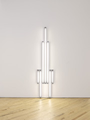 Seven fluorescent-white, tubular lights positioned against a white wall in the shape of a tower.