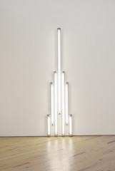 White fluorescent tubes are mounted in the shape of a tower on a wall.