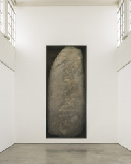A large gray-brown rock sits upright in a rectangular cutout of a white wall.