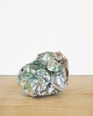 A crumpled ball-like sculpture made of reflective silvery green metal rests on a wooden floor.