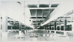 High-contrast, black-and-white photograph of nearly empty, large factory room with chairs, desks, and books in foreground and vertical columns evenly spaced throughout room.