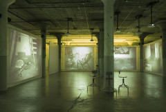 Large industrial space under green light with projection screens serving as walls, displaying images of a small room containing various debris including furniture.