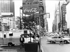 A busy metropolitan intersection is filled with cars and pedestrians in this black-and-white image.
