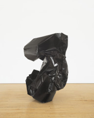 A crumpled sculpture made of black metal rests on a wooden floor.