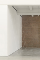 Five white threads, spaced evenly apart, are suspended between the top of the wall and the concrete floor.