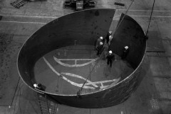 Seven people with safety helmets are gathered around and within two large, curved forms that overlap at one point to create a circular shape in this black-and-white image.