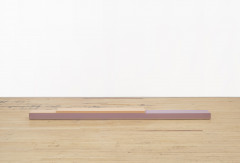 A thin, rectangular peach beam is stacked on a longer, pink beam on a wooden floor in front of a white wall.