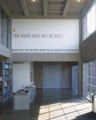 Orange, gray, and blue text outlined in black is placed high on a wall in a bookshop lobby. The text reads: