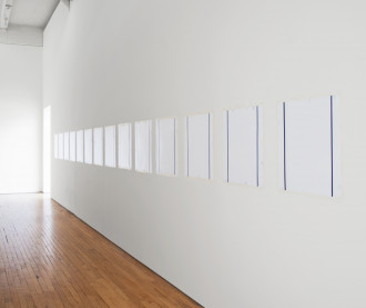 Angled view of a room where fourteen evenly spaced white squares are hung from a white wall. Two blue lines run vertically near the edges of each square.