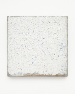 Square painting with thick, textured white paint with blue speckles showing through, on a tan canvas which is visible on the bottom edge.