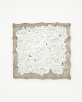 A square beige canvas with frayed edges is mostly covered in textured white paint with bits of green and black.