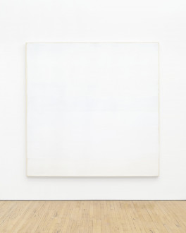 A large, square tan canvas painted white hangs low on a white wall above a wood floor. The canvas is slightly visible around the edges of the paint.