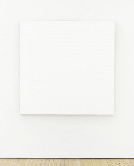 A large, square canvas painted entirely white hangs on a white wall above a wood floor.