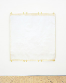 A square sheet of cream-colored paper painted off-white is taped to a white wall at the top and bottom edges. The edges are unpainted.