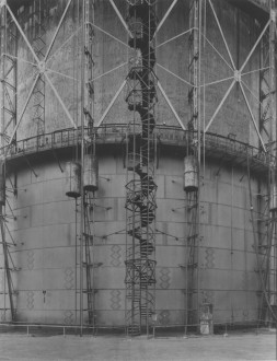 Close-up black-and-white photograph of a gas tank, showing geometric external ladders, staircases, and metal beams.