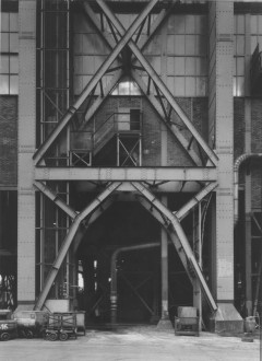 Black-and-white photograph of a glass and brick factory building behind a large metallic scaffolding.