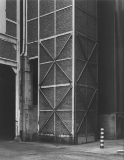Black-and-white photograph of a corner of a brick building's exterior featuring a lattice of vertical, horizontal, and diagonal metal beams affixed to the brick.