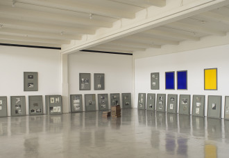 Framed photographs lean against a wall and in a corner. Seven frames with various photographs or blue or yellow paintings are installed above in addition to two stacks of copper and iron blocks.