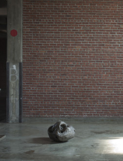 A gray, round sculpture sits on a concrete floor in front of brick wall.