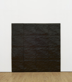 A square, black painting of sixteen glazed, ceramic titles is placed on a white wall above a wooden floor.