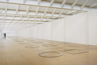 Twelve pairs of metal circles and squares laid flat on a wood floor.