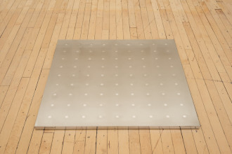 A square silver plaque featuring a grid of silver dots lies flat on a wood floor.