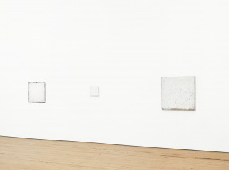 Three square white paintings hang on a white wall above a wood floor.
